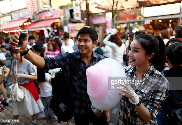 A couple pose for a selfie photograph using a smartphone while holding cotton candy on Takeshita Street in the Harajuku area of Tokyo Japan on...