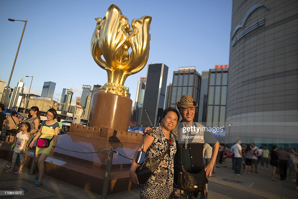 A couple pose for photographs in front of a sculpture of a gilded bauhinia at Golden Bauhinia Square in Hong Kong, China, on Tuesday, June 18, 2013. A shortage of housing, low mortgage costs and a buying spree by mainland Chinese have led home prices to more than double since the beginning of 2009, shrugging off repeated attempts by the government to curb gains amid an outcry over affordability. Photographer: Jerome Favre/Bloomberg via Getty Images
