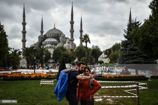 TOPSHOT A couple pose for selfie on August 22 2017 in front of the Sultanahmet mosque during a rainy day in Istanbul / AFP PHOTO / OZAN KOSE