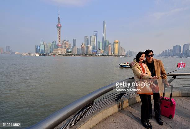 A couple pose for selfies with the New Pudong Area the Financial Center of Shanghai with the Oriental Pearl TV Tower in the background on February 25...