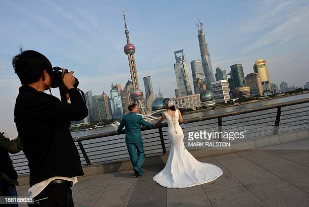 A couple pose for wedding photos on the historic Bund in Shanghai on October 29 2013 Divorce rates in China's two wealthiest cities Beijing and...
