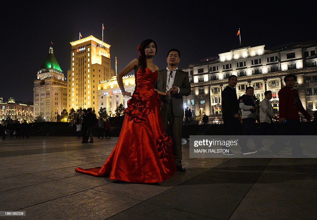 A couple pose for wedding photos on the historic Bund in Shanghai on October 29, 2013. Divorce rates in China's two wealthiest cities, Beijing and Shanghai, have soared after the announcement of a property tax that includes a loophole for couples who split up. Nearly 40,000 couples divorced in the Chinese capital in the first nine months of this year, jumping 41 percent on the same period in 2012, according to figures released by Beijing's civil affairs officials this month. AFP PHOTO/Mark RALSTON