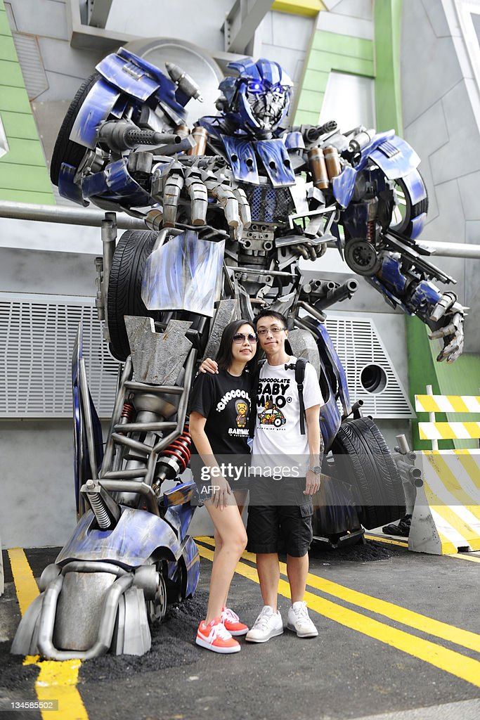 A couple poses beside a with a Transformers robot on the launch day of the new amusement park ride at Universal Studios Singapore on December 3, 2011. 'Transformers: The Ride' is based on the Transformers movie franchise directed by Michael Bay.