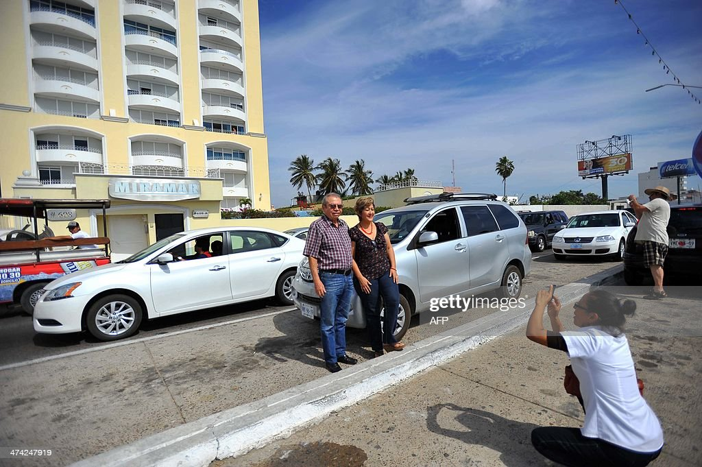 A couple poses for a photo in front of the Miramar condominium in Mazatlan, State of Sinaloa, Mexico on February 22, 2014, where Mexican drug trafficker Joaquin Guzman Loera aka 'el Chapo Guzman' was arrested early this morning by Mexican marines. Guzman is the Sinaloa cartel leader and the most wanted by US and Mexican anti-drug agencies. AFP PHOTO/Fernando Brito