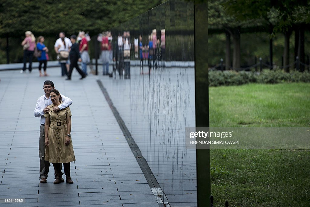 A couple poses for a photo on the Korean War Memorial on the National Mall October 17 2013 in Washington DC The US federal government reopened after...