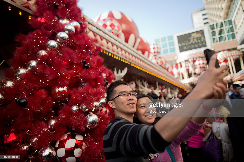 A couple poses for a photograph in front of a Christmas tree outside a shopping mall in the Tsim Sha Tsui area of Hong Kong, China, on Saturday, Dec. 22, 2012. Hong Kong's economy is set for its weakest annual expansion since the global financial crisis as the European sovereign debt crisis damps global trade. Photographer: Lam Yik Fei/Bloomberg via Getty Images