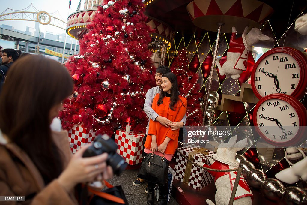 A couple poses for a photograph in front of Christmas decorations outside a shopping mall in the Tsim Sha Tsui area of Hong Kong, China, on Saturday, Dec. 22, 2012. Hong Kong's economy is set for its weakest annual expansion since the global financial crisis as the European sovereign debt crisis damps global trade. Photographer: Lam Yik Fei/Bloomberg via Getty Images