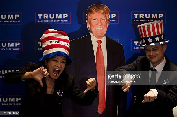 A couple poses for a picture next to a cardboard cut outs of US presidential candidat Donald Trump during an election event organised by the US...