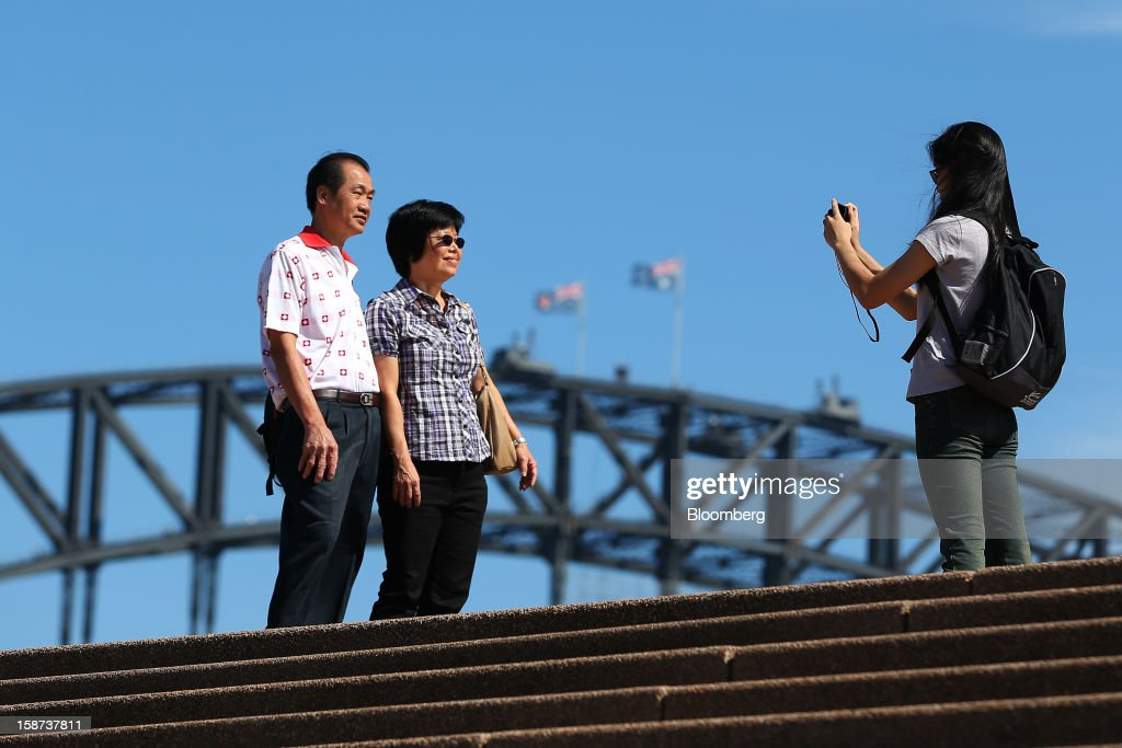 A couple poses for photographs in front of the Sydney Harbour Bridge in Sydney, Australia, on Monday, Dec. 24, 2012. At least 150,000 people from mainland China and across Asia are projected to descend on Sydney, Australia's most populous city, during the New Year's Eve and Chinese New Year period. Photographer: Brendon Thorne/Bloomberg via Getty Images