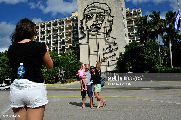 A couple poses for pictures at Revolution Square in Havana on November 27 2016 two days after the death of Cuban revolutionary leader Fidel Castro...