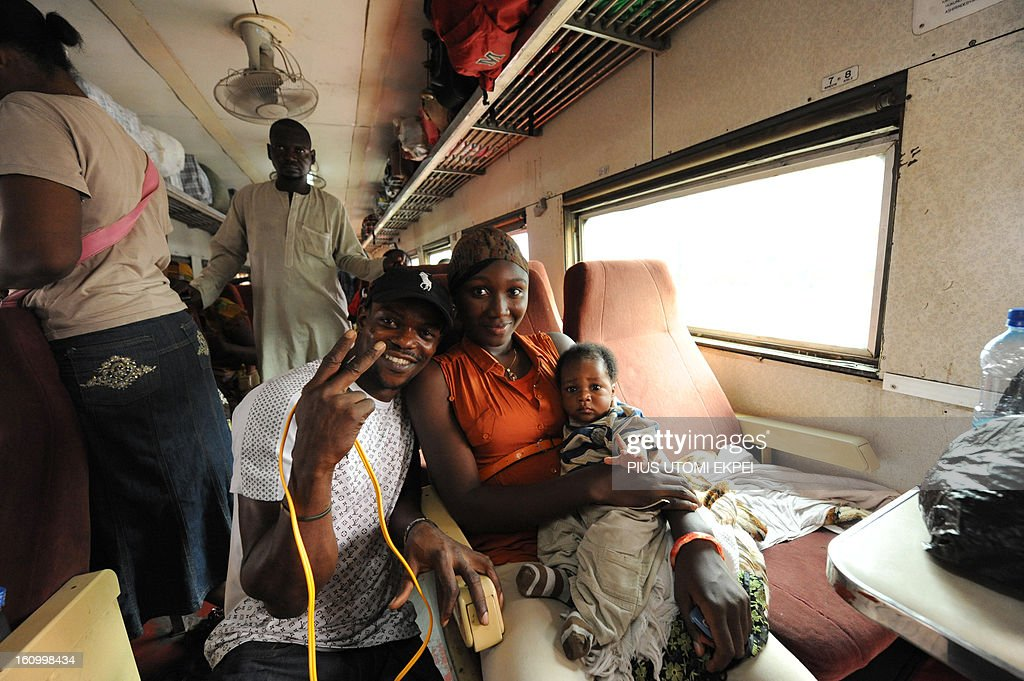 A couple poses in an air-conditioned first class coach of a train heading to Kano from Lagos Terminus of the Nigerian Railway Corporation on February 8, 2013. The rejuvenated Nigerian Railway Corporation has commenced operation of mass transit on the Lagos-Kano route, Nigeria's major commercial cities. The state-owned corporation which went into bankruptcy during the last 20 years due to lack of maintenance of infrastructure and high numbers of employees also began haulage of petroleum products from Lagos to the north of the country. Earlier last year, the Railway Corporation had acquired 20 pressurised tank wagons as it prepared to commence the fuel haulage. The 20 wagons have the capacity to lift 900,000 litres of petroleum products, the equivalent of 27 road tankers.