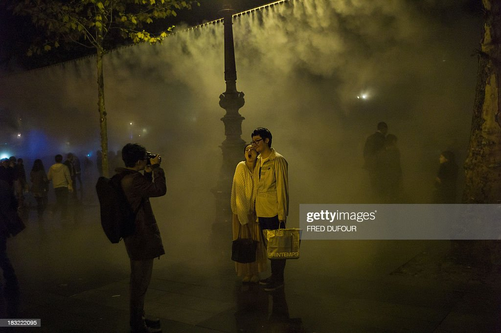 A couple poses next to an art installation by Japanese artist Fujiko Nakaya 'Fog Square', on October 5, 2013, at the Place de la Republique, in Paris, during Paris' Nuit Blanche (White Night) event.