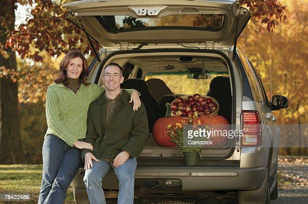 Couple posing at back of SUV loaded with apples and pumpkins