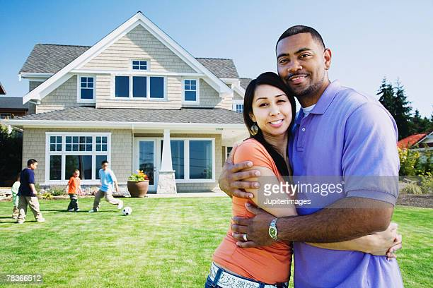 Couple posing by kids playing in front yard