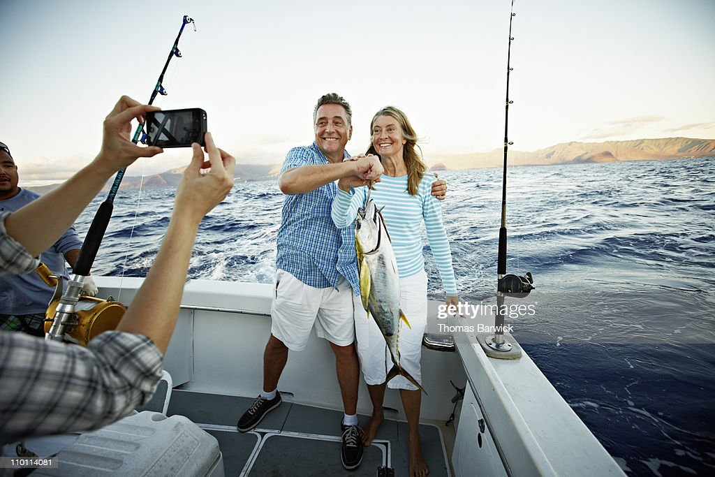 Couple posing for picture holding fish on boat