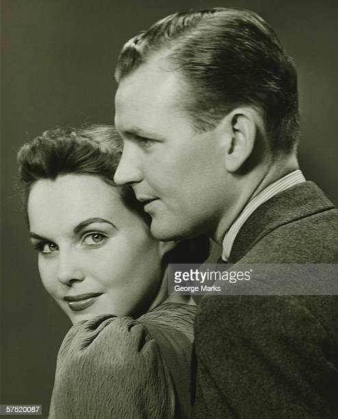 Couple posing in studio, (B&W), close-up, portrait