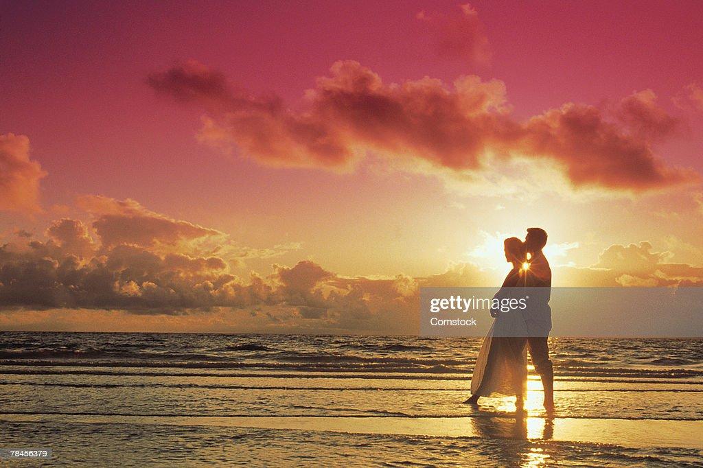 Couple posing on beach at sunset