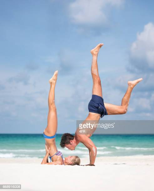 Couple practicing AcroYoga at the Beach