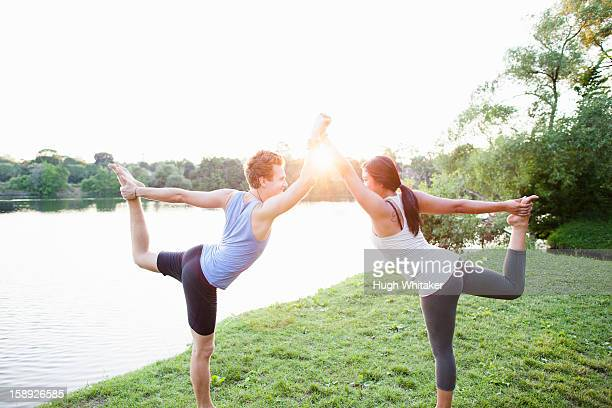 Couple practicing yoga by water