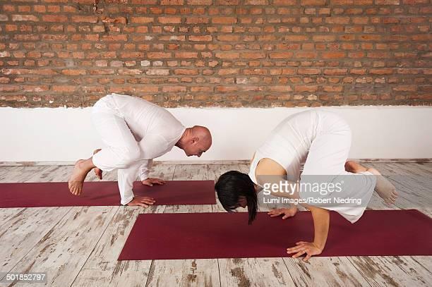 Couple practicing Yoga, Crow pose