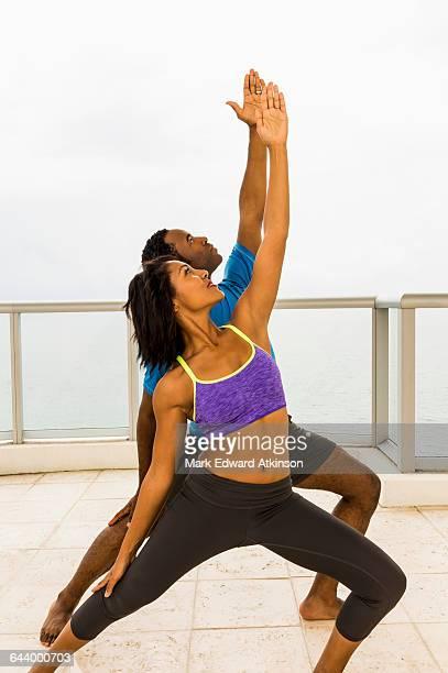 Couple practicing yoga on balcony