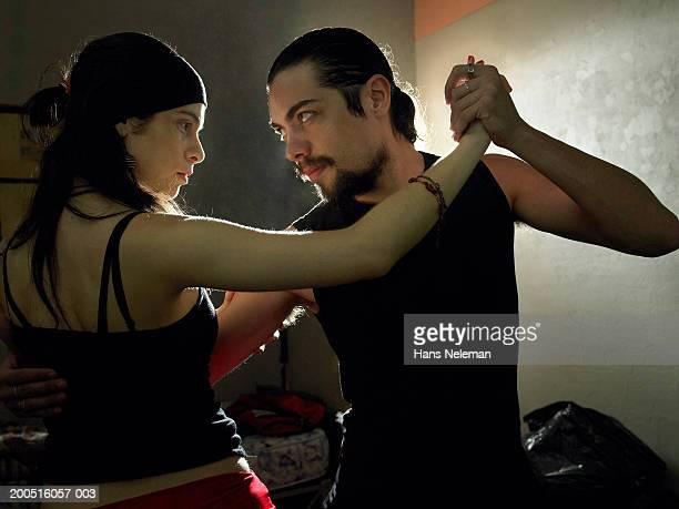 Couple practising tango in dark room, close-up, profile