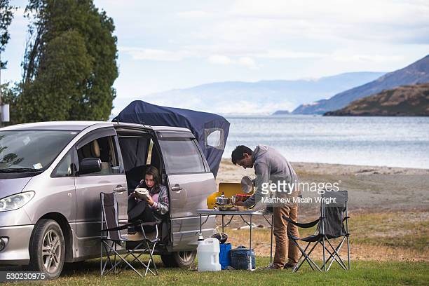 A couple prepares lunch at a campsite.