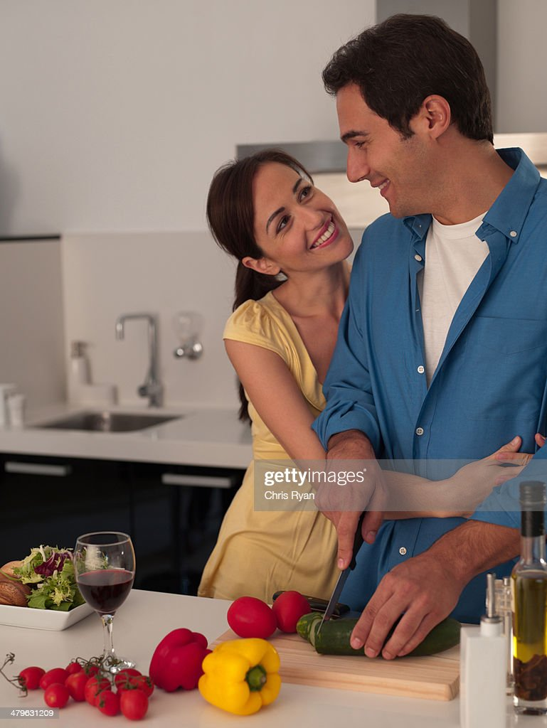 Couple preparing a meal together in modern kitchen : Stock Photo