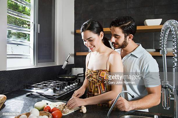 Couple preparing food at home in the kitchen.