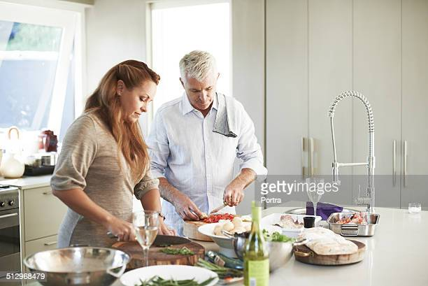 Couple preparing food at kitchen counter