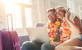 Young romantic couple wearing Hawaii accessories and sunglasses is preparing for travel at home. Sitting on sofa with laptop and credit card in hands while suitcases are standing nearby