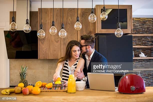 Couple préparation de jus d'orange dans la cuisine