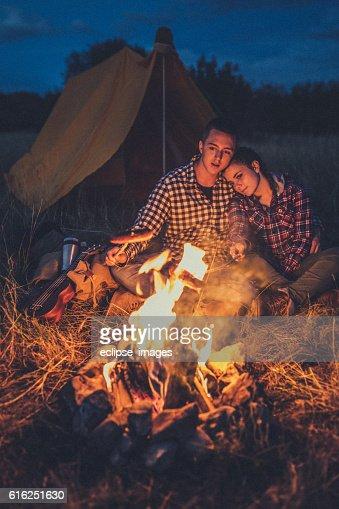 Couple preparing sausages on bonfire : Foto de stock