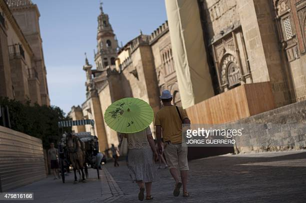 A couple protected from the sun with umbrella and hat walk along the Mezquita the MosqueCathedral of Cordoba on July 7 2015 In Spain started on July...