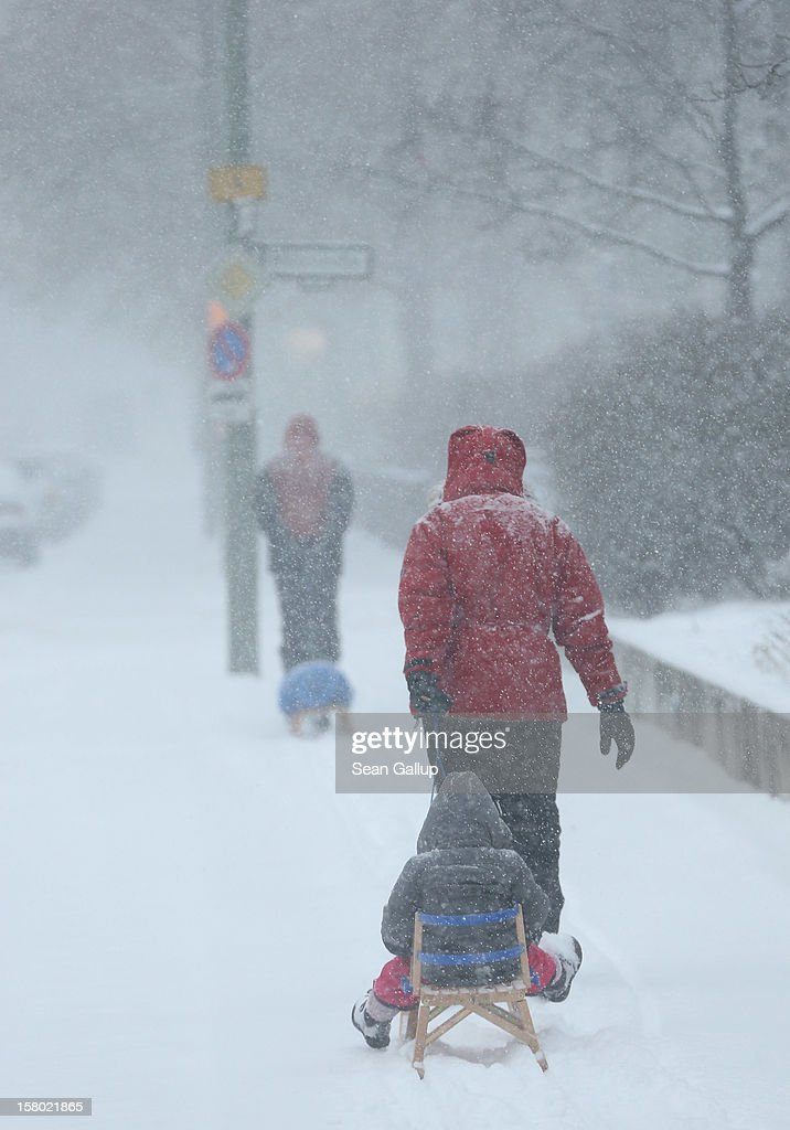 A couple pull children on sleds along a snow-covered sidewalk during a heavy snowfall in Zehlendorf district on December 9, 2012 in Berlin, Germany. Northeastern Germany was inundated with snow that covered highways and blanketed the region.