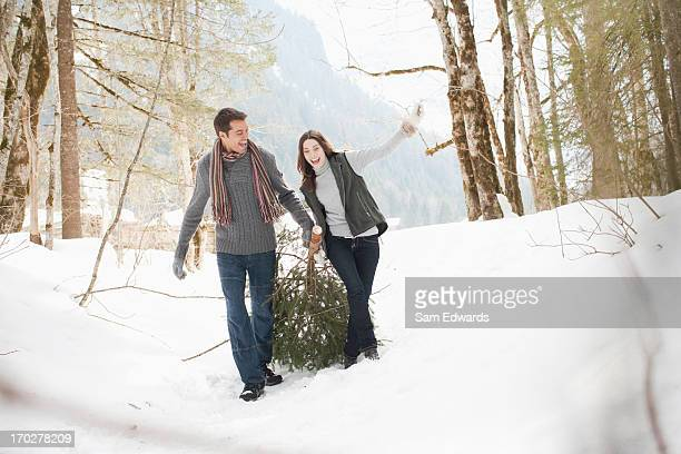 Couple pulling Christmas tree in woods