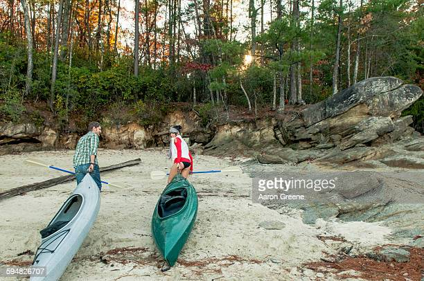Couple pulling kayaks on rocks