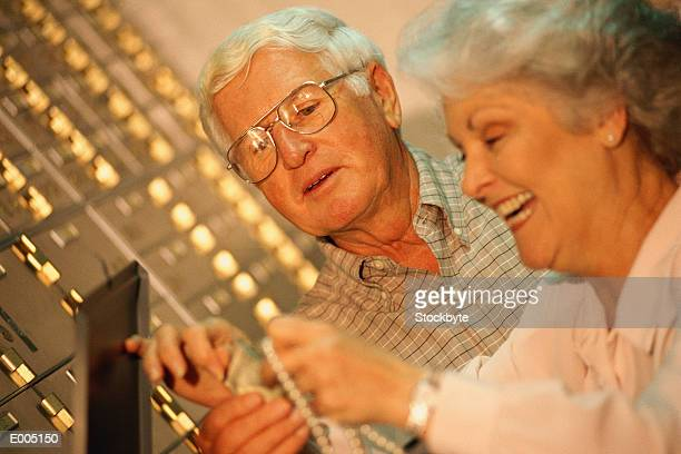 Couple pulling necklace from safety deposit box