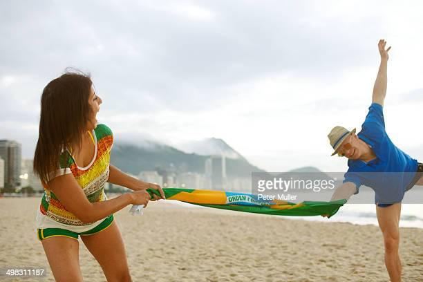 Couple pulling on flag on beach