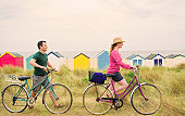 Couple push bicycles over beach