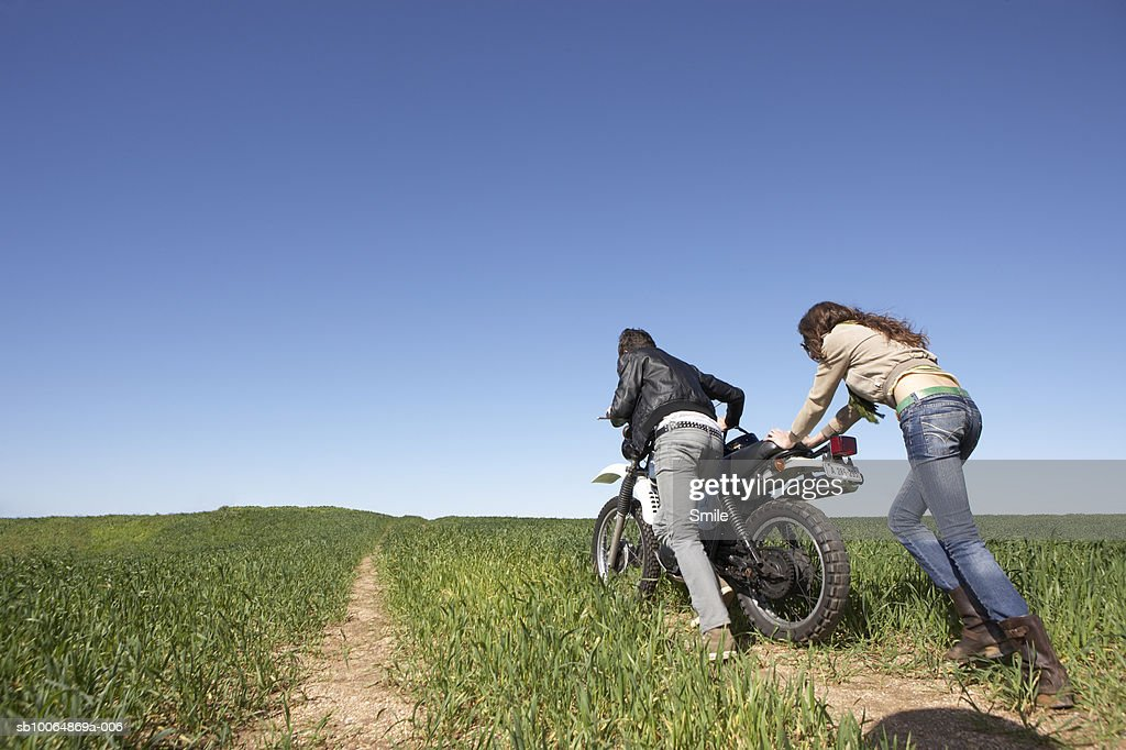 Couple pushing bike on dirt track, low angle view : Stock Photo