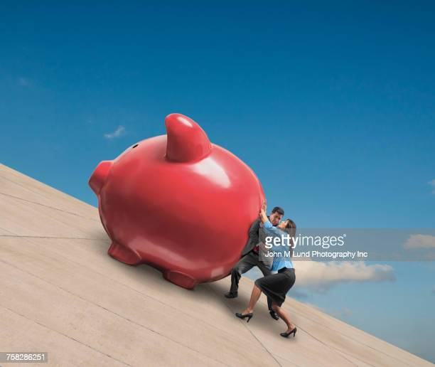 Couple pushing red piggy bank uphill