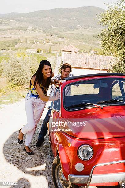 Couple pushing vintage vehicle , Tuscany , Italy