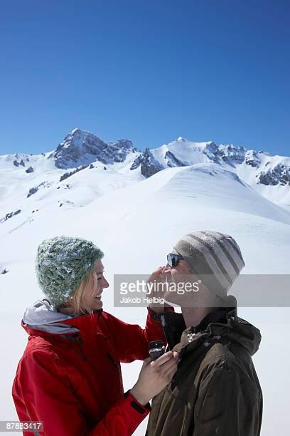 Couple putting on suntan lotion