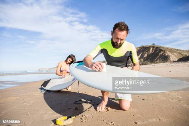 Couple putting paraffin on their surfboards on the beach