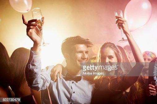 Couple raising champagne flutes on dance floor