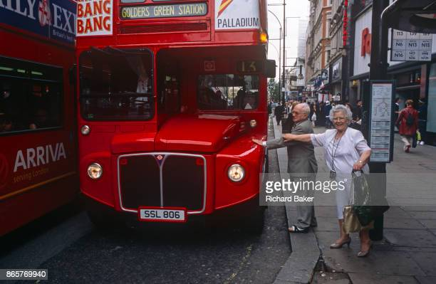 A couple reach out to touch an iconic but ageing red London Routemaster bus on 18th April 2002 on Oxford Street London England