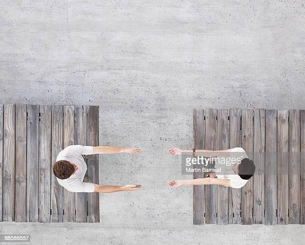 Couple reaching across gap