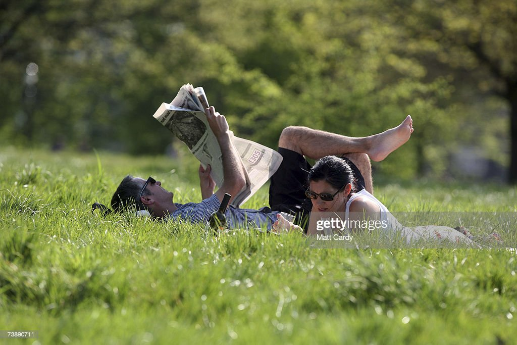 A couple read as they enjoy the hot weather in Primrose Hill on April 15, 2007 in London. The un-seasonably warm weather has heralded the start to what weather forecasters predict will be a record breaking summer.
