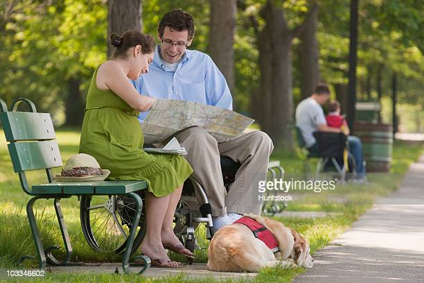 Couple reading a map and a service dog lying in a park